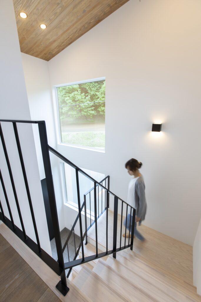 シンプルでありながらゆったり幅のある階段大きな窓には森林が見えます。
